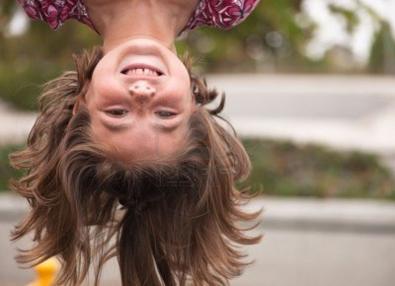 7282068-a-close-up-of-a-young-girl-hanging-up-upside-down-with-a-big-smile
